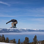 featured image showing a snowboarder catching air with Lake Tahoe in the background