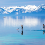 featured image showing two people paddle boarding on Lake Tahoe with Snow on the Sierras