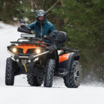 featured image showing a Man driving a quad bike in the winter