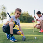 featured image showing two kids learning to play golf outdoors