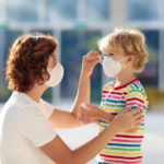 featured image showing a mother helping her son put on a mask during a COVID-19 outbreak
