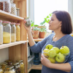 featured image showing Woman with bowl of green apples in pantry, organizing in kitchen
