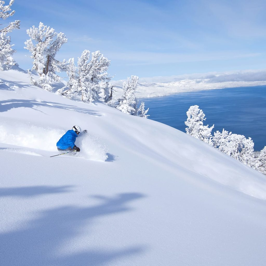 Featured image showing a downhill skier cutting fresh tracks in several feet of powder, overlooking Lake Tahoe, CA