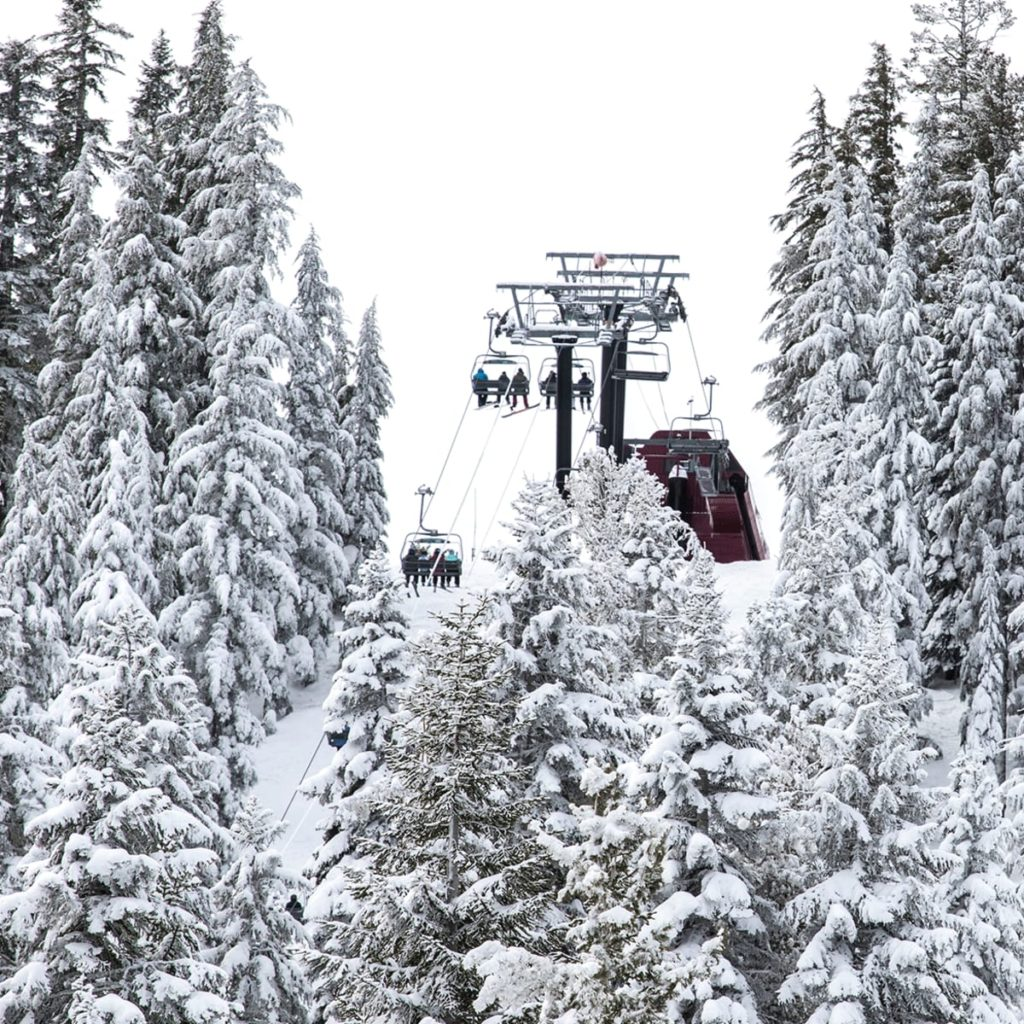 Inline image showing riders on a chairlift atop the trees on a snowy day at Northstar Ski Resort in California